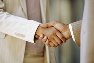 close-up of a businessman shaking hands with a businesswoman --- Image by © Royalty-Free/Corbis